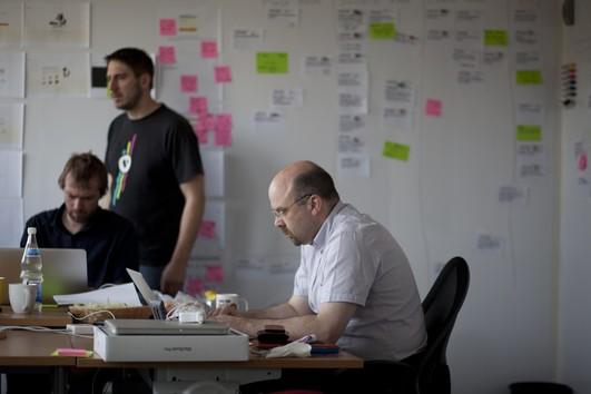 Ein Team aus drei Kollegen arbeitet an einer effizienteren Entwicklung